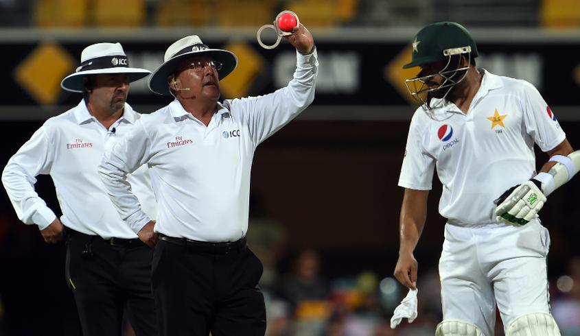 ICC umpires inspect the pink ball during a day/night test match