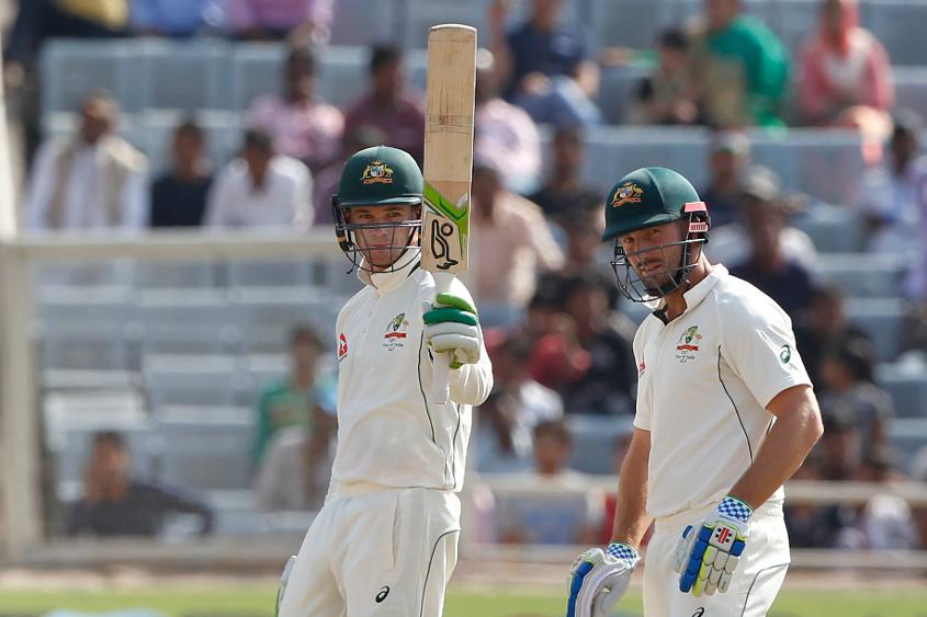 Peter Handscomb raising his bat after reaching his 50
