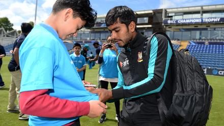 Mehedi Hasan of Bangladesh signs an autograph for a young kid during the ICC Champions Trophy Cricket for Good clinic at Cardiff, Wales.