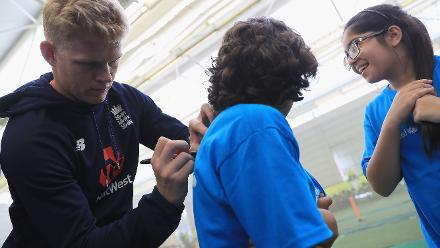 Sam Billings of England signs an autograph for a young school kid during an ICC Champions Trophy Cricket for Good clinic at Birmingham.
