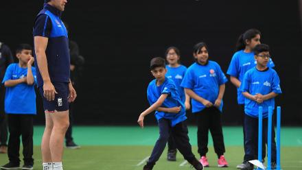 David Willey of England looks on as a young kid gets ready to bowl during an ICC Champions Trophy Cricket for Good clinic at Birmingham.