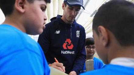 Steven Finn of England signs an autograph for a young school kid during an ICC Champions Trophy Cricket for Good clinic at Birmingham.