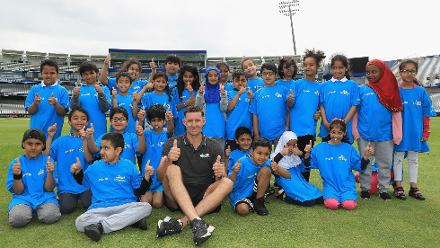 Mike Hussey poses for a picture with local children at the Cricket For Good coaching clinic at Birmingham.