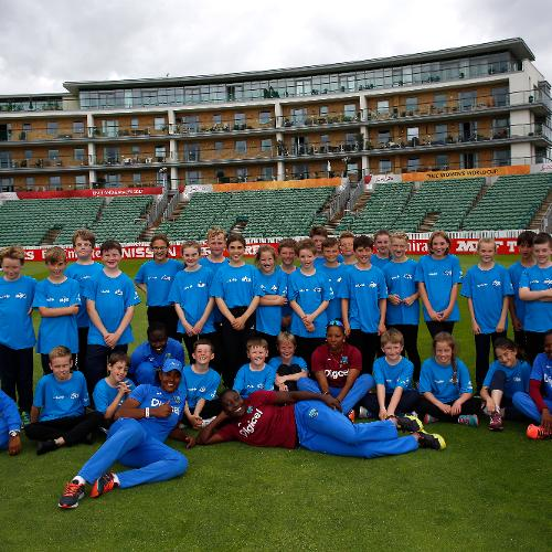 West Indies players pose for a group picture with local school children during an ICC Cricket for Good clinic
