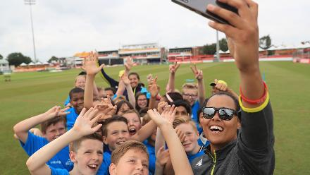 Chloe Tryon of South Africa takes a selfie with local school children during an ICC Cricket for Good clinic at Grace Road