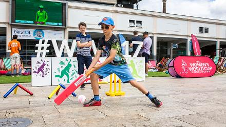 Kids play cricket with the England-Australia match screening in the background at the First ICC Women's World Cup Fan Park.