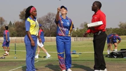 Petro Enright tosses the coin while Fatuma Kibasu looks on