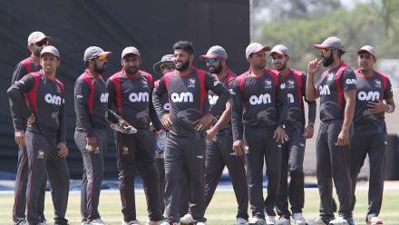 UAE players await the arrival of a Namibian batsman.