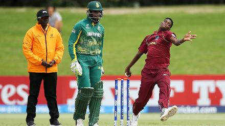 Jarion Hoyte of the West Indies bowls while Jiveshan Pillay of South Africa looks on