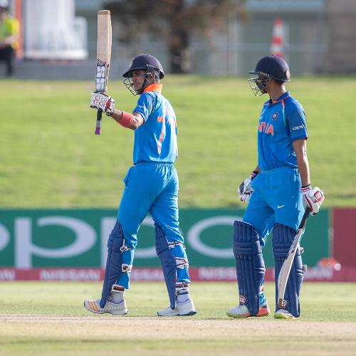 Shubman Gill of India raises his bat as he celebrates scoring half century