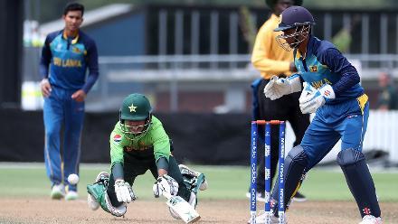Muhammad Taha of Pakistan dives for his crease