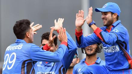 Mujeeb Zadran of Afghanistan (L) is congratulated by team mates after dismissing Jakob Bhula of New Zealand