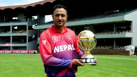Nepal captain Paras Khadka holding the ICC Cricket World Cup Qualifer trophy on the outfield of Queens Sports Club.