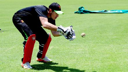 Wicket Keeper Peter Moore fully focused on the ball.