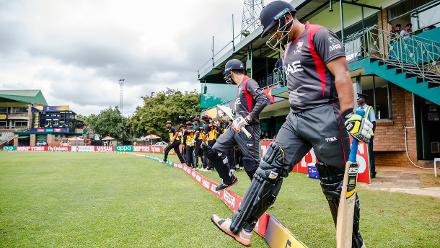 UAE batsman Ashfaq Ahmed (R) with captain Rohan Mustafa (L) enter the pitch during a group A World Cup Qualifier match between Papua New Guinea and the United Arab Emirates at Harare Sports Club March 4 2018.