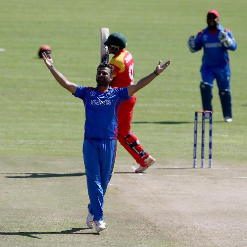 Dawlat Zadran (L) of Afghanistan celebrates taking the wicket of Cephas Zhuwao of Zimbabwe during the ICC Cricket World Cup Qualifier between Zimbabwe and Afghanistan at Queens Sorts Club on March 6, 2018 in Bulawayo, Zimbabwe (©ICC).