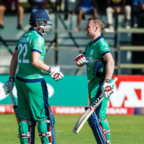 Ireland captain William Porterfield celebrates his century with team mate Kevin O'Brien in action during a Group A World Cup Qualifier cricket match between Papua New Guinea and Ireland at Harare Sports Club, March 6 2018 (©ICC).