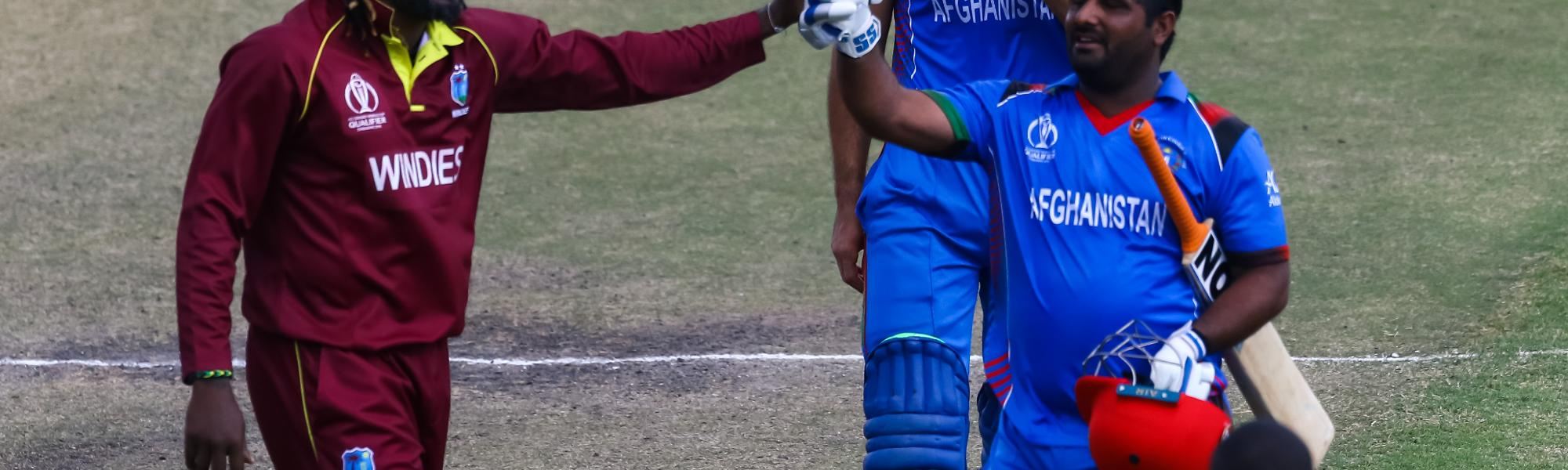 Afghan batsman M.Shahzad receives a consiliatory high five from Chris Gayle as he leaves the pitch after making 84 runs during the ICC Cricket World Cup Qualifier Trophy, Harare Sports Club March 25 2018 (©ICC).