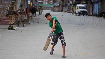 Shortlist - Faisal Khan (Freelance for Anadolu Agency) - A boy lifts his cricket bat to strike a ball on a deserted street during a curfew in Srinagar, overseen by officers from India's Central Reserve Police Force, 13 July 2017, India