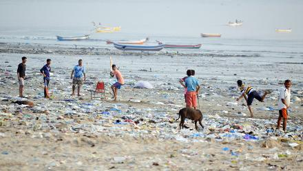 Shortlist - Uday Devrukhkar (Amateur) - Children enjoy a match amongst the accumulated litter on Versova beach, using makeshift cricket gear with a chair for stumps and a canine fielder, 30 December 2017, Mumbai, India