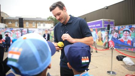 Mitchell McClenaghan, the New Zealand paceman, signs autographs for young cricket fans