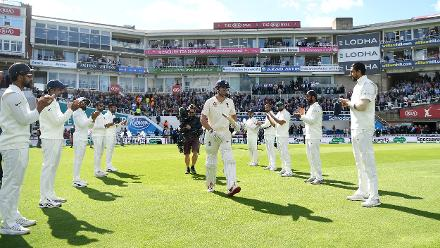 A guard of honour from the Indians as he walks out to bat on the first day