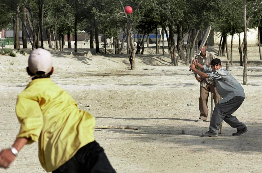 Afghan youths play cricket in a public park of Kabul