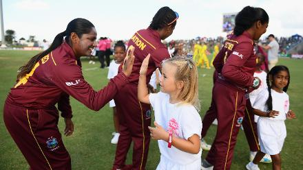 A young mascot receives a high five from members of the Windies side during the ICC Women's World T20 2018 Semi-Final match between Windies and Australia at Sir Viv Richards Cricket Ground on November 22, 2018 in Antigua, Antigua and Barbuda.