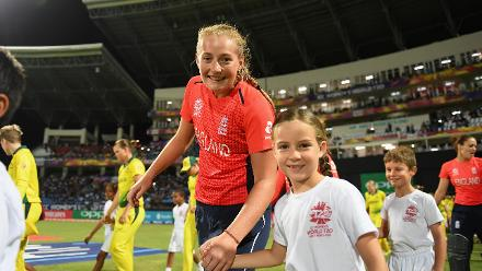 Sophie Ecclestone of England makes her way towards the national anthems with a young mascot during the ICC Women's World T20 2018 Final between Australia and England at Sir Vivian Richards Cricket Ground on November 24, 2018 in Antigua.