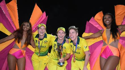 Ellyse Perry, Sophie Molineux and Elyse Villani of Australia celebrate with the trophy alongside dancers during the ICC Women's World T20 2018 Final between Australia and England at Sir Vivian Richards Cricket Ground on November 24, 2018 in Antigua.