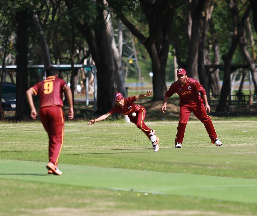 A Qatar fielder dives for the ball