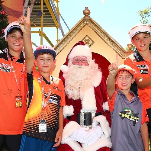 Young cricket fans pose with Santa Claus during a Big Bash League game between Perth Scorchers and Melbourne Stars