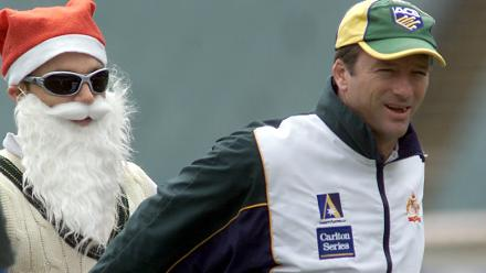 Michael Slater of Australia dressed as Santa Claus helps Steve Waugh warm up during training at the MCG