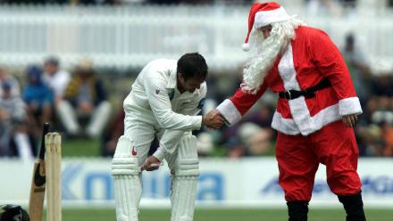 New Zealand's Nathan Astle shakes hands with Santa Claus during a practice match against Prime Ministers XI at Manuka Oval