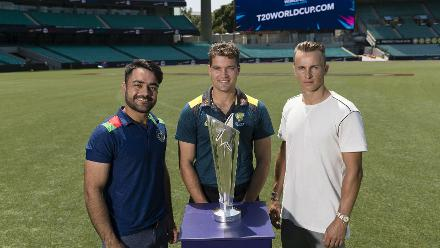 Rashid Khan, Alex Carey and Tom Curran pose with the ICC T20 World Cup 2020 trophy during the fixture announcement event