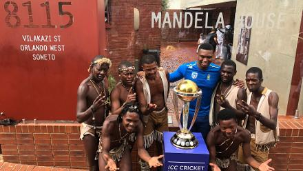 Lungi Ngidi poses with the CWC Trophy in front of the Mandela House. Street performers came by as well.