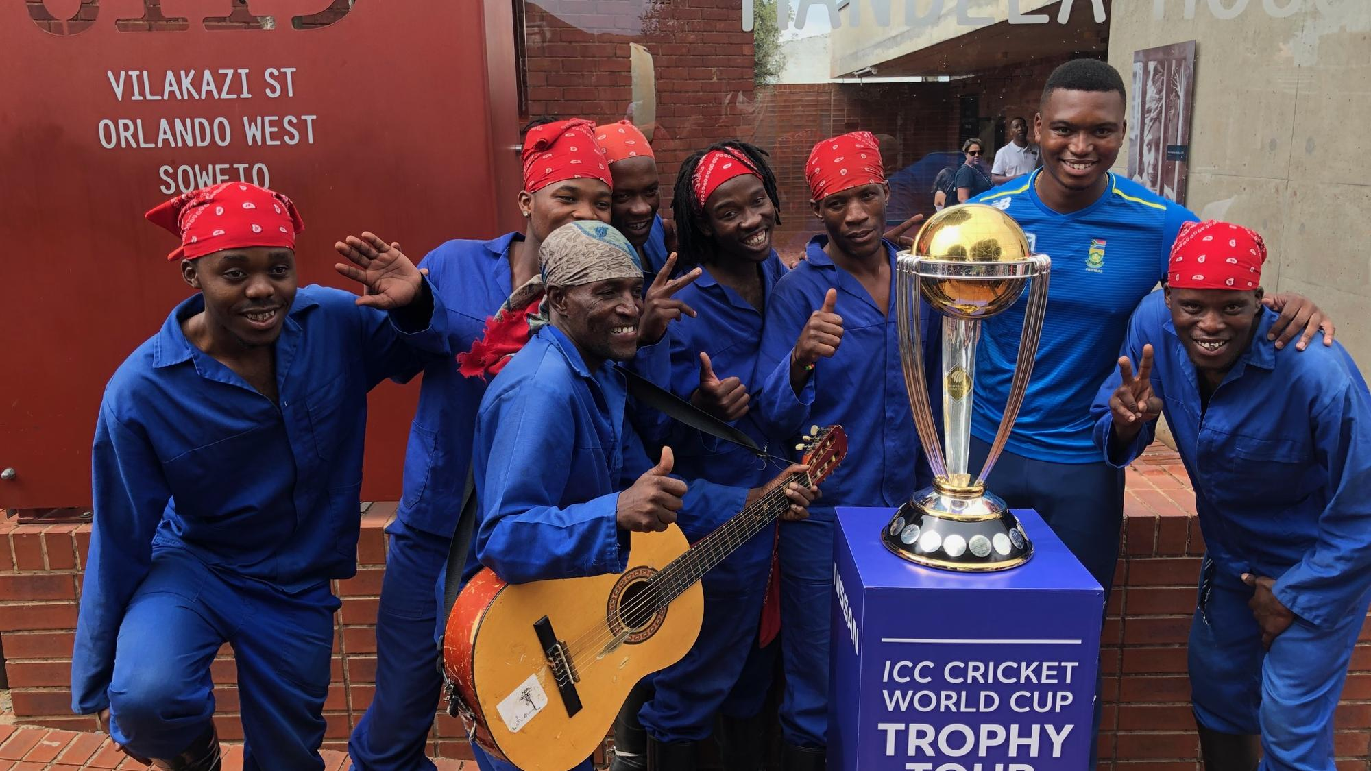 Lungi Ngidi and artistes pose with the CWC Trophy in front of the Mandela House